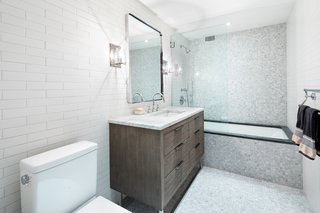 The first-floor bathroom is fitted with Carrara marble countertops, polished chrome Kohler fixtures, and a large Restoration Hardware vanity with cypress cabinetry.