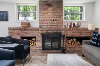 The brick on the wood-burning fireplace has been left exposed and offers a striking contrast to the surrounding white walls.