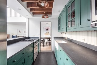 The kitchen features cheerful, sea-green cabinetry.