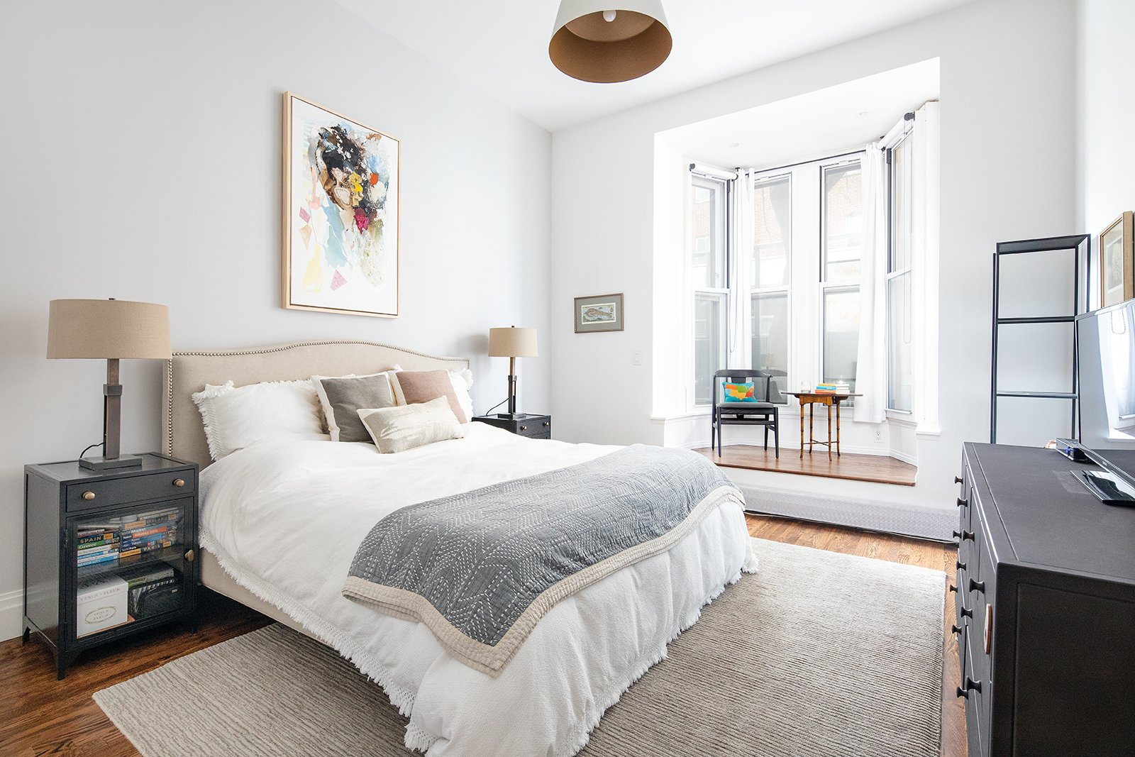Bedroom, Rug Floor, Table Lighting, Pendant Lighting, Medium Hardwood Floor, Bed, Chair, and Night Stands A look at the master bedroom.  Photo 12 of 14 in An Updated 1845 Brooklyn Home Hits the Market at $2.95M