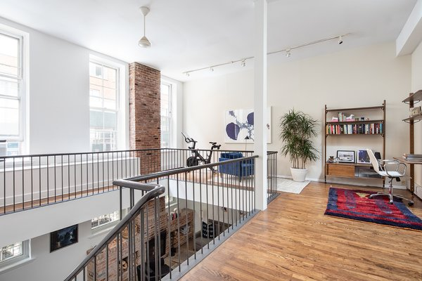 The wraparound mezzanine has a massive skylight. This space could be used for a variety of purposes, including being converted into a fourth bedroom.