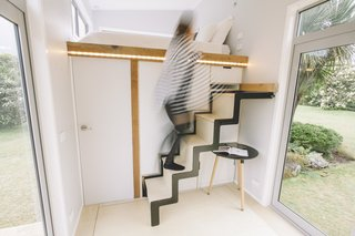 The retractable aluminum staircase can slide into a cabinet when not in use.