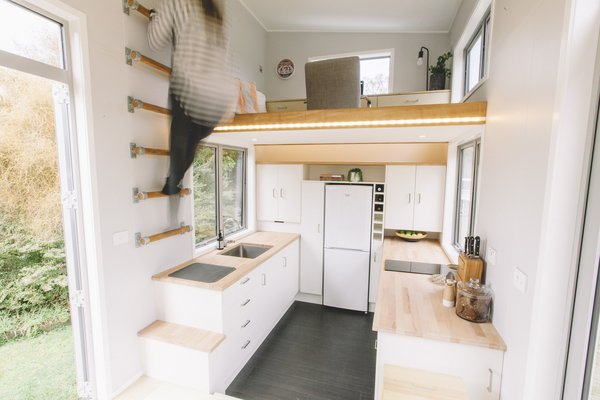 A wall-mounted ladder provides access to the office loft.