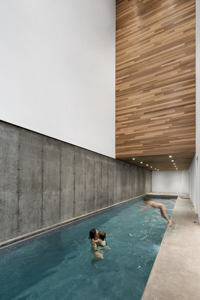 The indoor pool room pairs cool concrete with warm wood accents.
