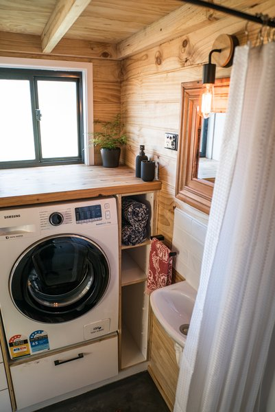 In the bathroom/laundry is a full size shower and toilet with stunning, stone-like epoxy floor, and a small sink.