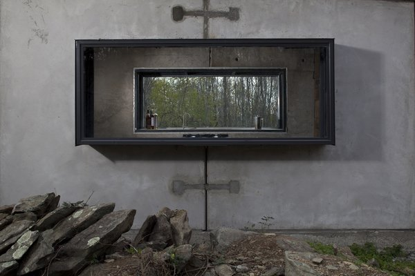 The concrete cabin has a steel chimney and steel window frames.