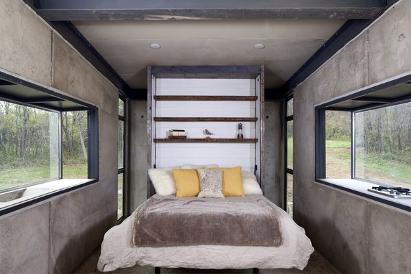 The reclaimed-wood Murphy bed, the wood-burning fireplace, and leather rugs and throw pillows add warmth and coziness to the pared-back interiors.