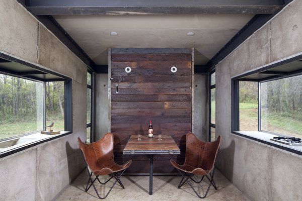 The concrete walls, floors, and ceilings are raw and exposed, creating a modern, industrial-inspired canvas.