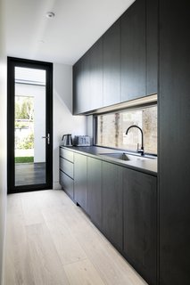 The open-plan kitchen features durable Neolith benchtops, a smoked glass backsplash, and cabinetry with a carbon-colored timber veneer.