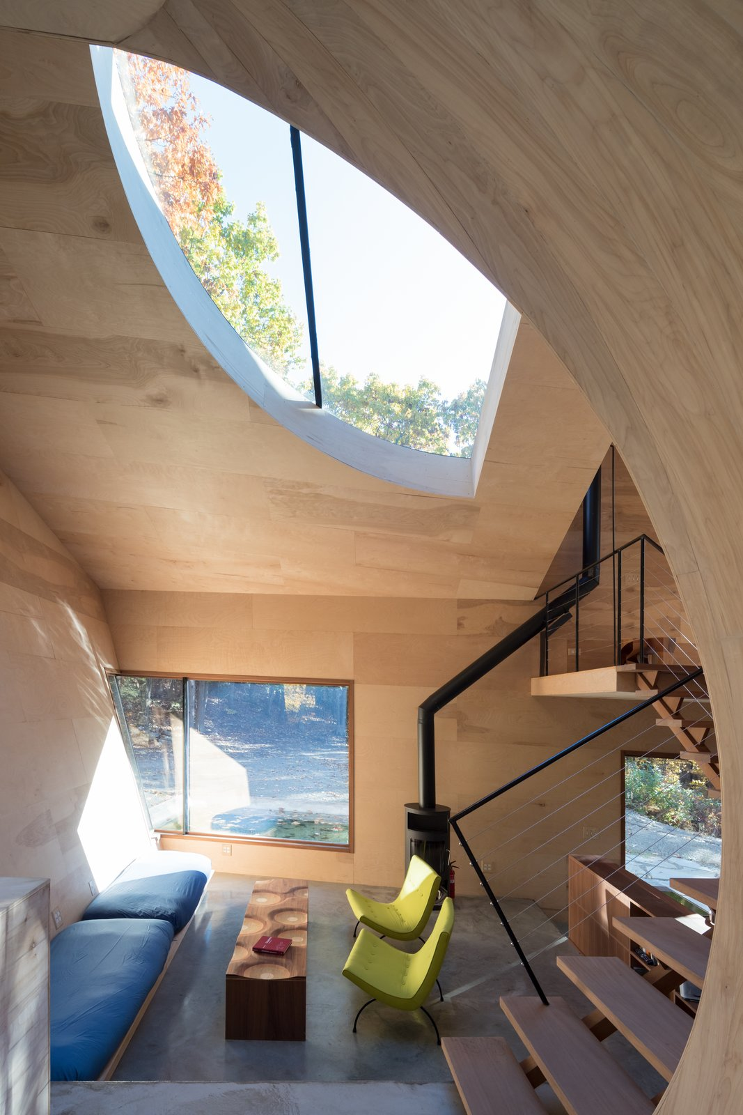Living Room, Wood Burning Fireplace, Coffee Tables, Bench, Chair, and Concrete Floor Ex of In House by Steven Holl Architects, Interior, Living   Photo 9 of 17 in The Compact, Solar-Powered Ex of In House Sits Lightly Upon the Land