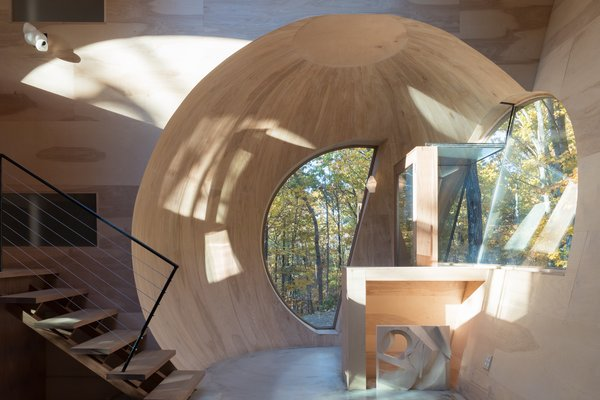 The geometry of the spherical intersections becomes apparent at the entry porch, where an orb of wood welcomes visitors.