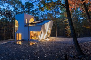 Situated amid the forest in Rhinebeck, New York, the geometric, eco-friendly Ex of In House by architect Steven Holl stars a large window capable of heating the living space with sunlight during the winter months. In the summer, a shade ensures it keeps cool. In accordance with the home's sustainable mission, the interiors are finished with natural oiled wood and plywood, and all light fixtures were 3D-printed in PLA cornstarch-based plastic.