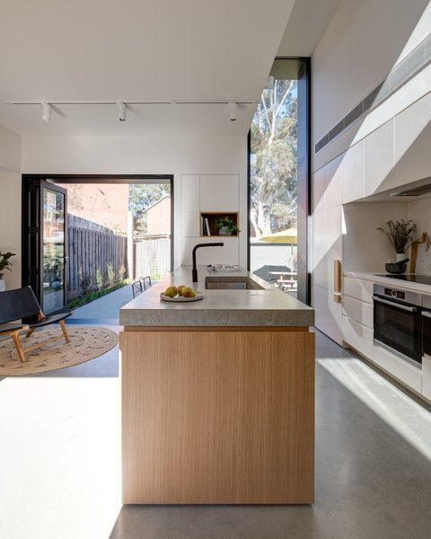 A polished concrete island top contrasts with oak timber cabinetry in the kitchen.