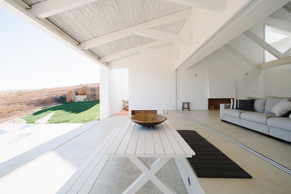 Open-air patios are located at all four corners of the house, and three bedrooms are set along three sides of the square.