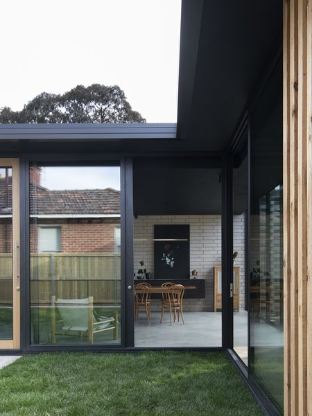 The extension sits on a burnished concrete slab with exposed concrete bricks along the main wall.