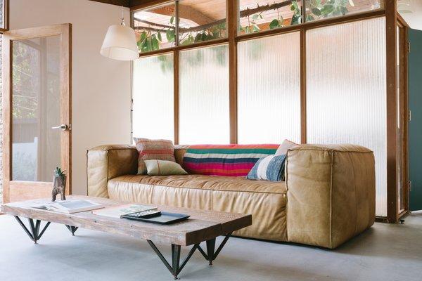 A RH Fulham leather sofa, a Garza Marfa striped blanket and HD Buttercup cushions.