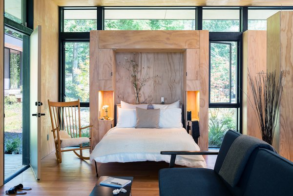 In this living area, a built-in Murphy bed can be pulled down to create a flexible sleeping area when needed. This Murphy bed incorporates two small bedside nooks with built-in lighting.