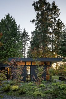 Cedar platforms near the ground extend beneath broad eaves to create spaces that frame outdoor views.