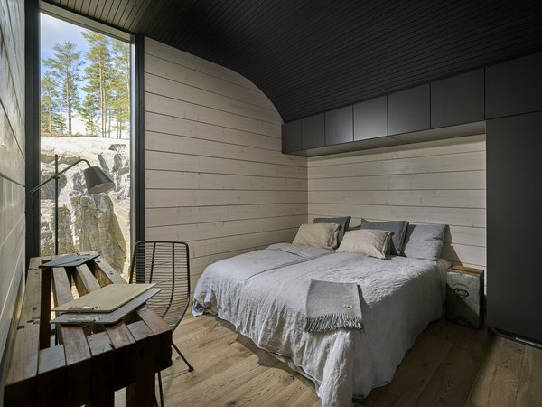 Additional bedrooms located on the opposite site of the home look out toward a forest.
