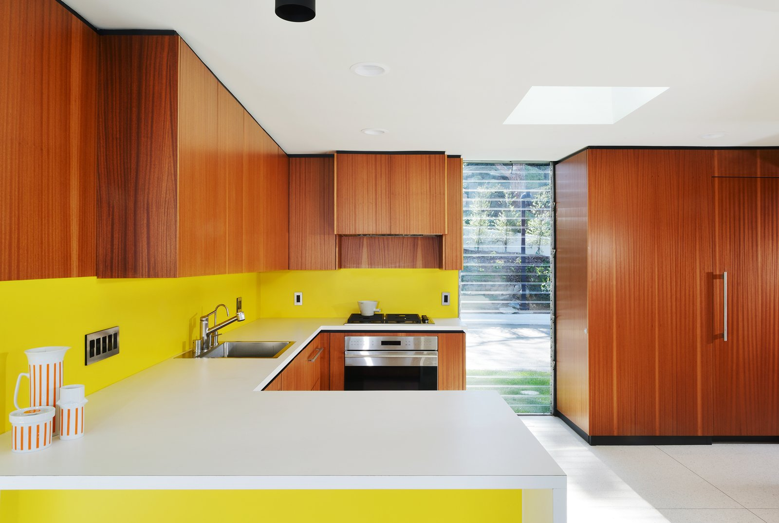Casa Kundera kitchen with yellow accents and walnut walls