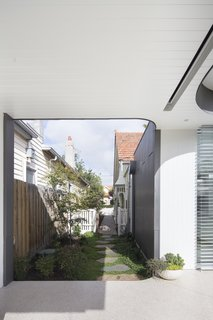 From the front gate, the owner can walk through a side garden towards the glass doors of the extension.