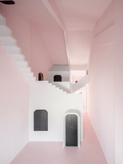 """Dream is painted a soft pink. All the """"mundane"""" components of daily life, such as lighting fixtures and electronic appliances, have been concealed behind a series of black doors."""