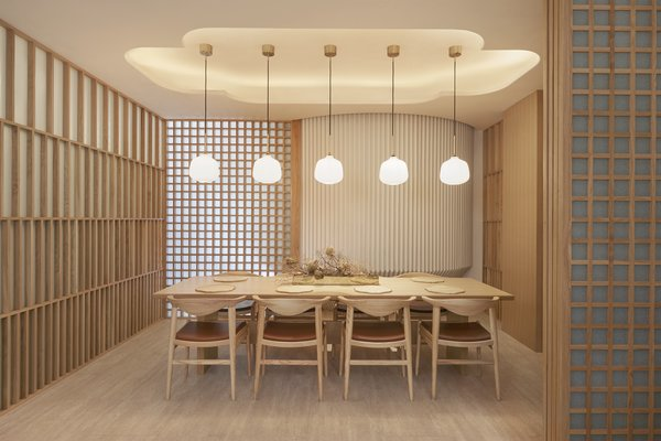 Pendant lights from Rubn hang over a private dining space, and textured plaster walls from Armourcoat echo the wooden screens.