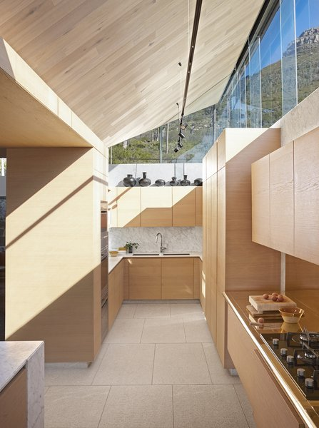 Home to Greg Truen, director of South African architecture and design firm SAOTA, Kloof 119A is a 9,150-square-foot residence in Cape Town that takes advantage of mountain and city views while de-emphasizing the street and neighboring homes. Kitchen joinery was done by Roma Casa Kitchens. Clerestory windows allow mountain views and light to drench the space.