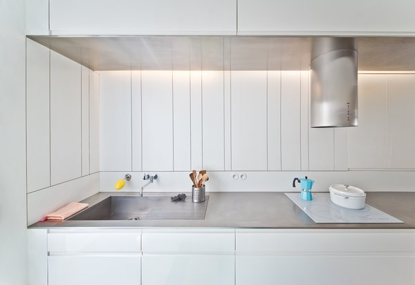 Stainless steel counters stretch across the length of the kitchen.