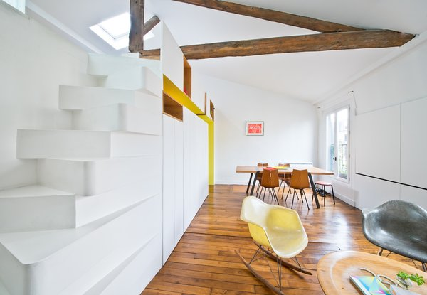 """""""The staircase is a great space saver, and we worked to give it an unusual presence,"""" says Delauney. """"It seems challenging to climb to some, even though it is actually very comfortable. This helps define the space on the mezzanine as tucked away from the rest of the apartment, harder to reach, and private."""""""