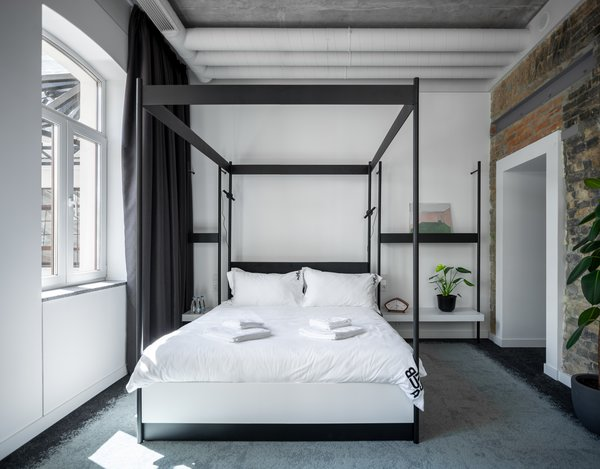 Exposed ceiling pipes give this bright bedroom a cool, industrial aesthetic.