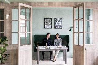 A dining nook features a green Settle bench by Sue Skeen for The New Craftsmen.