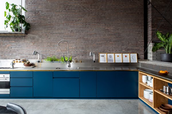 Vibrant blue cabinets brighten up this kitchen and serve as a bold contrast to the exposed brick. The stainless-steel countertop wraps slightly up the wall, and creates a trough for storing items.