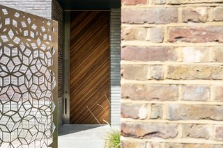 Metal, brick, and wood harmonize near the entrance of the house.