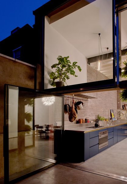 Large, pivoting glass doors connect the kitchen with a patio.