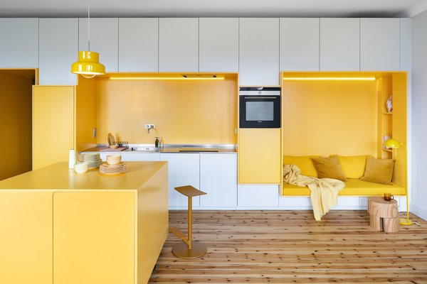 """When the owners of this 850-square-foot apartment in Stockholm's Södermalm neighborhood called upon local architect David Lookofsky to revive their 1920s apartment, they tasked the founder of the eponymous firm with incorporating more storage into the compact space. So, Lookofsky created a seven-meter-long kitchen wall with built-in cabinetry and a seating nook, all painted with a bright, egg-yolk yellow. """"In smaller apartments, kitchens often become a kind of social hub, both in everyday life or when you have people visiting,"""" says Lookofsky. """"You want these spaces to reflect the people who use them and support interactions and everyday life."""""""
