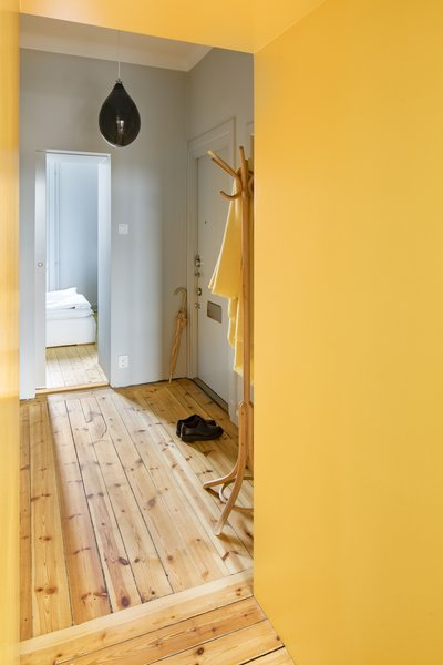 The entrance to the apartment is also painted a cheerful yellow.
