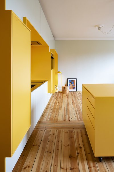 "A bright, yellow ""function wall"" saves space and visually expands this compact apartment."