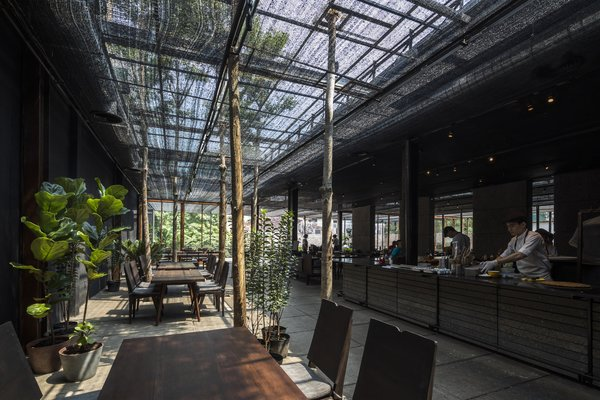 To shield the interiors from strong sunlight, this restaurant in central Ho Chi Minh City is clad in an agricultural net made from polyethylene that was initially developed for agricultural purposes, but quickly found its way into vernacular buildings because of its cost-effectiveness. NISHIZAWAARCHITECTS experimented with the netting, using shadow and light to help compose space.