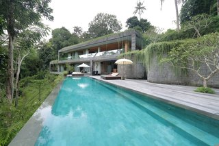 Sited on a steep hill overlooking lush tropical jungle and a river, this private villa is set on different levels that appear as if they are part of the natural landscape. The architecture follows the contours of the land, allowing for in-between spaces and gardens that would otherwise be difficult to enjoy.
