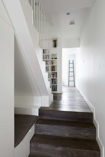 A reading nook is built into one of the walls along the stairs.