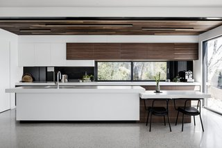 Spotted gum accents an otherwise white kitchen. The countertop drops down at one end to turn into a breakfast bar.