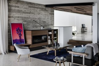 A Fameg Armchair B-1234 and Sean Dix Forte Rectangular Glass Coffee Table from Remodern adorn the living room.