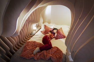 The Woom Room bed frames, which consist of multiple pieces of plywood slotted together like jigsaw pieces, are individually assembled by a team of EJ Ryder workers to reflect the curvature and coziness of the womb.