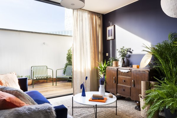 The living room in the penthouse opens to a sunlit terrace.