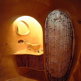 The bathroom features a sculptural sink and shower.