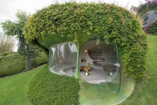 """Architect Javier Senosiain created this remarkable home on a hilly site near Mexico City. """"The green dune wraps itself around the inside spaces almost completely, rendering it almost invisible so that, from the outside, all one sees are grass, bushes, trees, and flowers,"""" he says."""