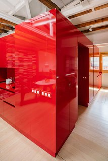 To reduce cost, Pardo constructed this glossy red volume using kitchen furniture units, so the clothing drawers are the same type used for cutlery in the kitchen nook, and the same sink model was used for both the kitchen and bathroom.