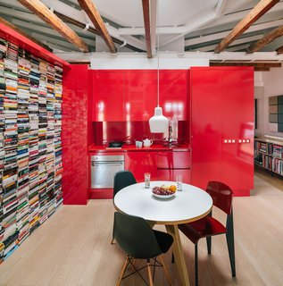 The red furniture system, which does not extend all the way up to the ceiling, works as a frame that structures the interiors. It contains the kitchen and bathroom, and also provides ample storage for Rubio's books, designer furniture, and decor.