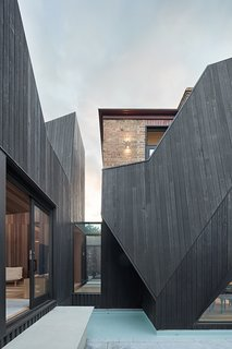 The bold, geometric forms provide a dramatic contrast to the historical frontage.